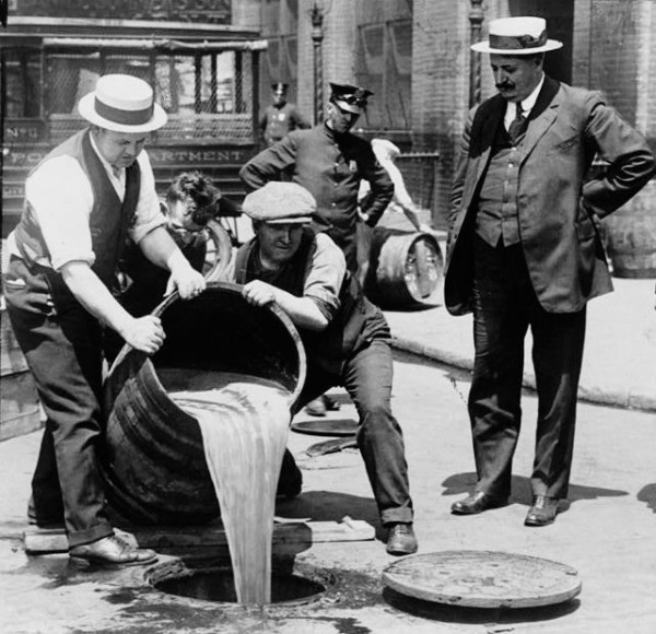 Men dumping beer barrels at the onset of Prohibition