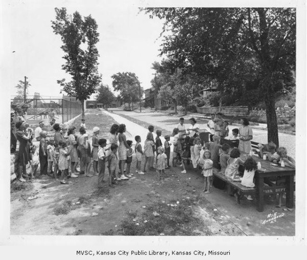 """Participants in the Summer Playground Feeding Program lined up at Mulkey Square Park."" 1942.Image courtesy of Missouri Valley Special Collections, Kansas City Public Library"