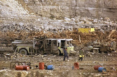 Investigators search through a highway construction site, Nov. 29, 1988 in Kansas City, Missouri where two early morning explosions shattered windows over a 10-mile area and killed six firefighters. The firefighters had been fighting a possible fire in a truck, officials said. (AP Photo/Sam Harrel)