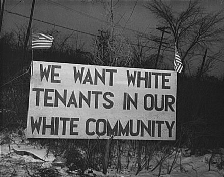"""Sign with American flag 'We want white tenants in our white community,' directly opposite the Sojourner Truth homes, a new U.S. federal housing project in Detroit, Michigan. A riot was caused by white neighbors' attempts to prevent Negro tenants from moving in."""