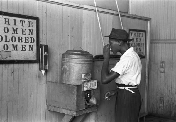 """A Black American drinks from a segregated water cooler in 1939 at a streetcar terminal in Oklahoma City."" Image courtesy of Library of Congress"